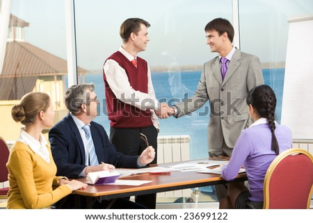 Photo of successful co-workers shaking hands while their partners looking at them - stock photo