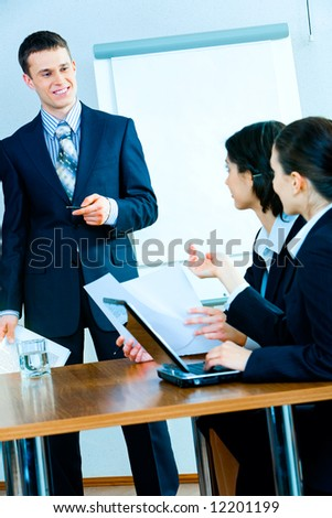 Photo of successful man in suit standing near whiteboard with pen and paper in hands and looking at businesswomen sitting at table and asking him questions - stock photo