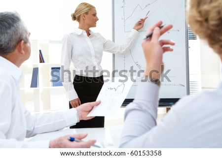 Photo of successful manager standing by whiteboard while her colleagues listening to her - stock photo