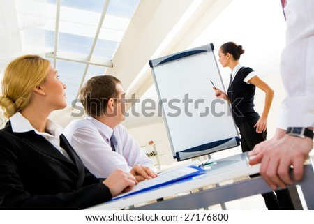 Photo of successful manager standing by whiteboard while the others listening to her - stock photo
