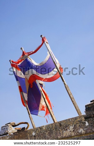 photo of Tattered Thailand flag over blue sky - stock photo