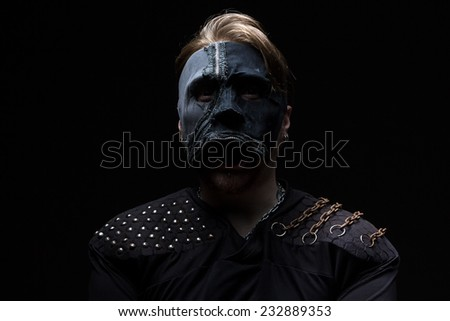 Photo of the blond man in mask on black background - stock photo