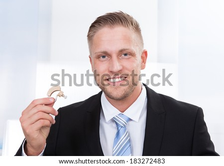 Photo of the businessman holding hearing aid - stock photo