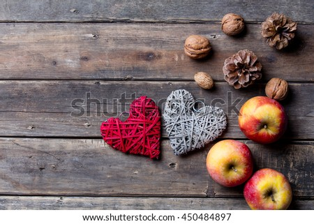 photo of the delicious apples, fir-cones, nuts, and red and grey heart shaped toys on the brown wooden background - stock photo