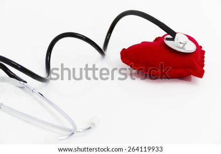 Photo of the Doctor's stethoscope listening to a healthy red heart, health concept, taking care about health - stock photo
