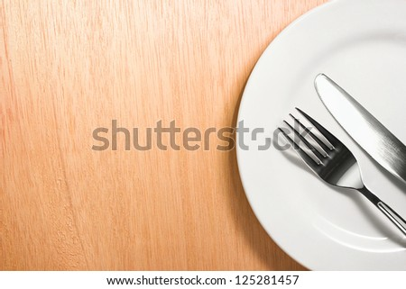 Photo of the fork and knife with white plate on wooden background - stock photo