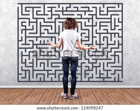 Photo of the girl before a wall with a labyrinth - stock photo