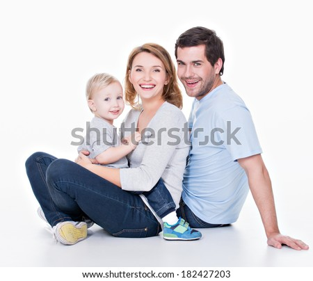 Photo of the happy young family with little child sitting on the floor - isolated on white background. - stock photo