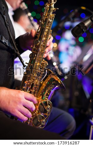 Photo of the male jazz saxophonist playing in sax - stock photo