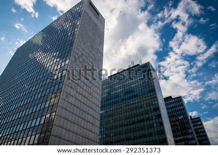 Photo of the office buildings with glass windows. Sky in the background. - stock photo