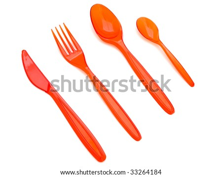 Photo of the red plastic fork knife and spoons against the white background - stock photo
