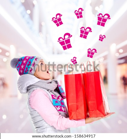 Photo of the surprised woman with gifts after shopping to the new year at shop - stock photo