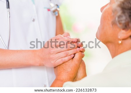 Photo of the young doctor hands protects the elderly woman hands - stock photo