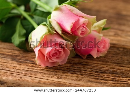 Photo of three beautiful tender roses placed on old worn wooden board with significant grooves and texture. - stock photo