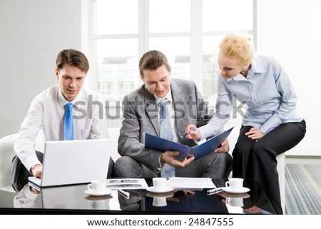 Photo of three employees planning their work together in office - stock photo