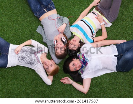 Photo of three woman sitting on grass while looking - stock photo