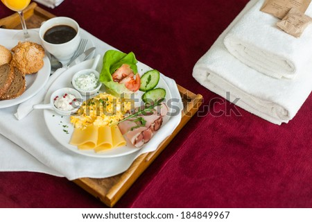 Photo of tray with breakfast food on the bed inside a bedroom - stock photo
