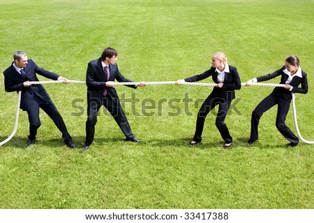 Photo of tug of war between business people - stock photo