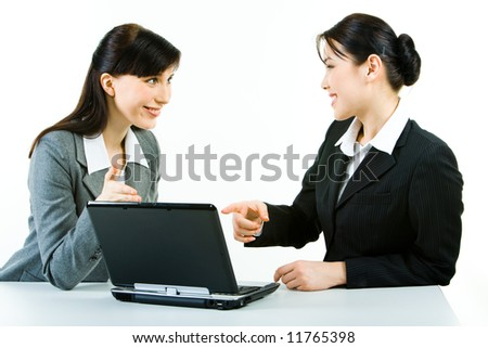 Photo of two attractive women pointing at the laptop monitor with smiles looking at each other - stock photo