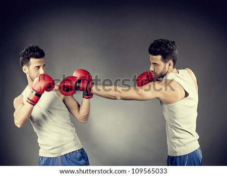 photo of two boxer who are fighting on a grey background - stock photo