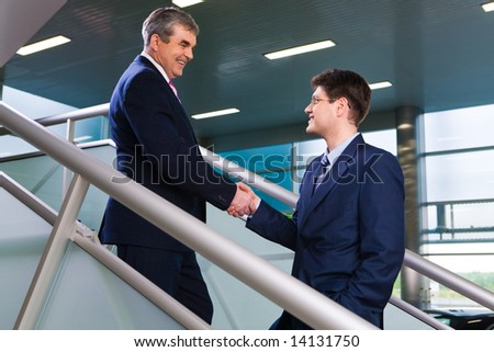 Photo of two business partners greeting each other by handshake on the stairs of office building - stock photo