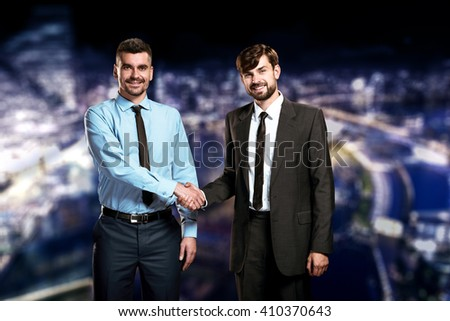 Photo of two businessmen on night cityscape background. Businessmen shaking hands and smiling - stock photo