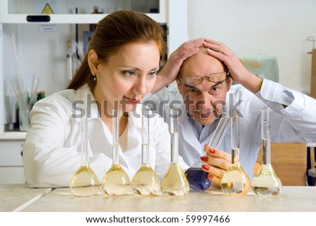 photo of two chemists, who make experiments in the chemistry lab. - stock photo