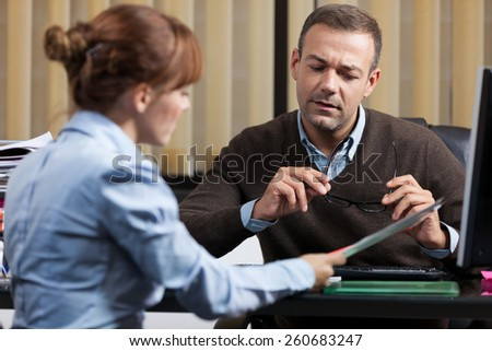 photo of two colleagues working together in the office - stock photo