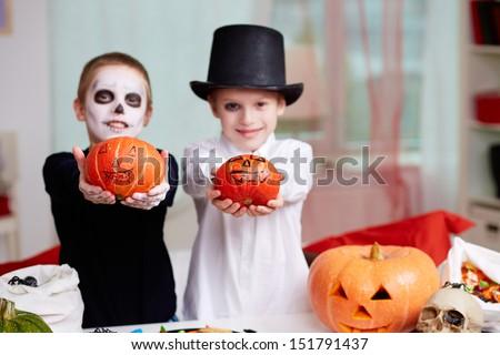 Photo of two eerie boys showing Halloween pumpkins - stock photo