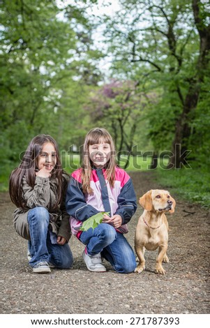 Photo of two girls posing with a dog - stock photo