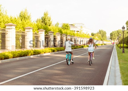 Photo of two lovers riding bicycle in the park and holding hands - stock photo
