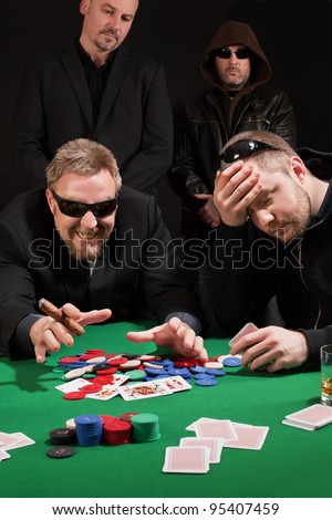 Photo of two male poker players, one winning and the other losing, while security watches over their shoulders. Cards have been altered to be generic. - stock photo