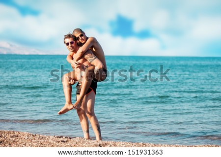 photo of two men in love hugging each other in front of the sea - stock photo