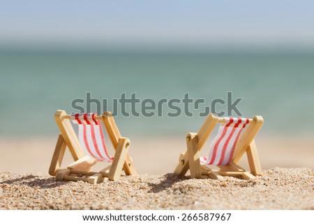 Photo Of Two Miniature Deckchairs On Sandy Beach - stock photo