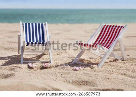 Photo Of Two Miniature Deckchairs On Sunny Beach - stock photo