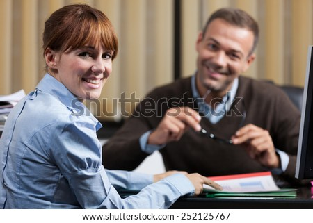 photo of two smiling colleagues in the office looking towards the camera - stock photo