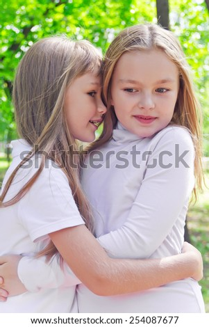 Photo of two smiling whispering girls in summer - stock photo
