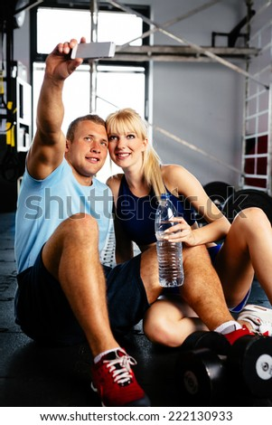 Photo of two sportspeople taking a selfie in a fitness center - stock photo