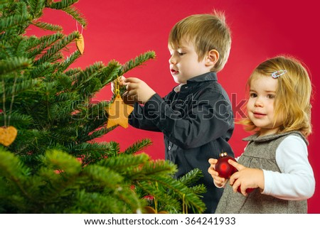 Photo of two young children, brother and sister, hanging decorations on a Christmas tree. - stock photo