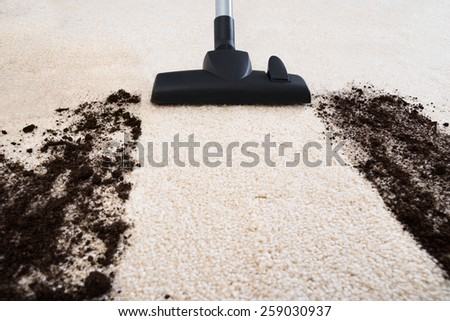 Photo Of Vacuum Cleaner Cleaning Dirt On Carpet - stock photo