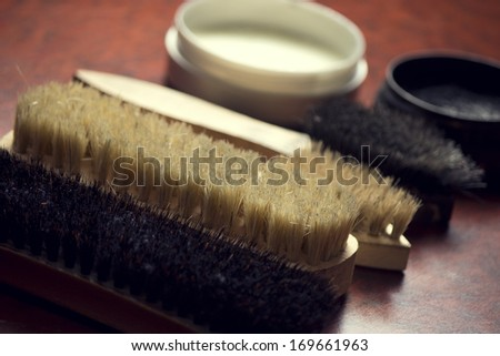 Photo of various brushes on wooden table used for polishing shoes  - stock photo