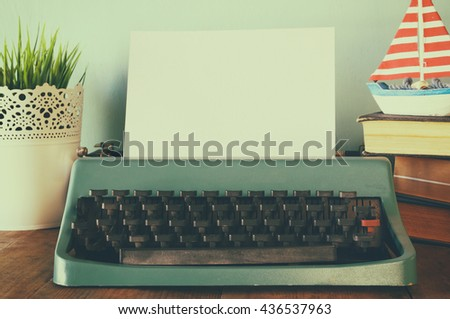photo of vintage typewriter with blank page on wooden table. retro filtered image - stock photo