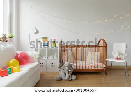 Photo of white and cosy newborn room interior - stock photo