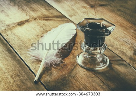 photo of white Feather and inkwell on old wooden table. retro filtered image  - stock photo