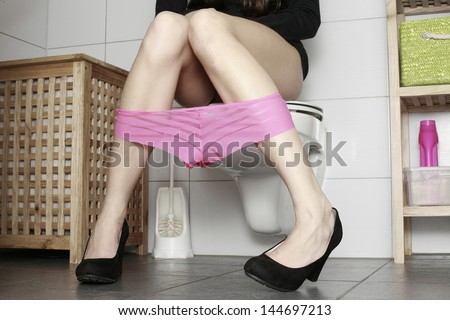 Photo of woman sitting on a toilet. with pink panties - stock photo