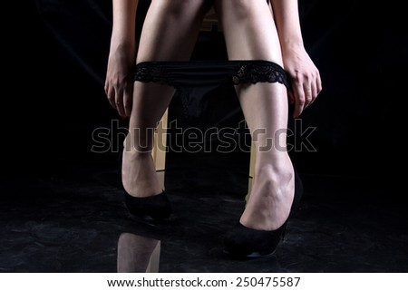 Photo of woman taking off panties on black background - stock photo