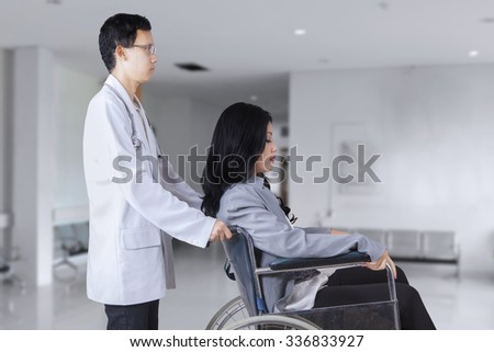 Photo of young asian doctor pushing patient on wheelchair in the hospital corridor - stock photo