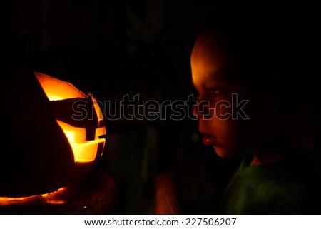 Photo of young boy looking at halloween pumpkin - stock photo