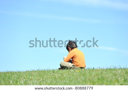 Photo of young boy sitting on the grass  and looking down. He is thinking and sad abandoned lonely - stock photo