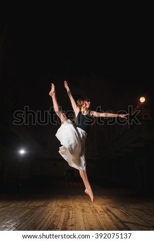 Photo of young brunette dancer girl, ballerina in white skirt in split jump on stage in theater with spotlight. barefoot dancer. - stock photo